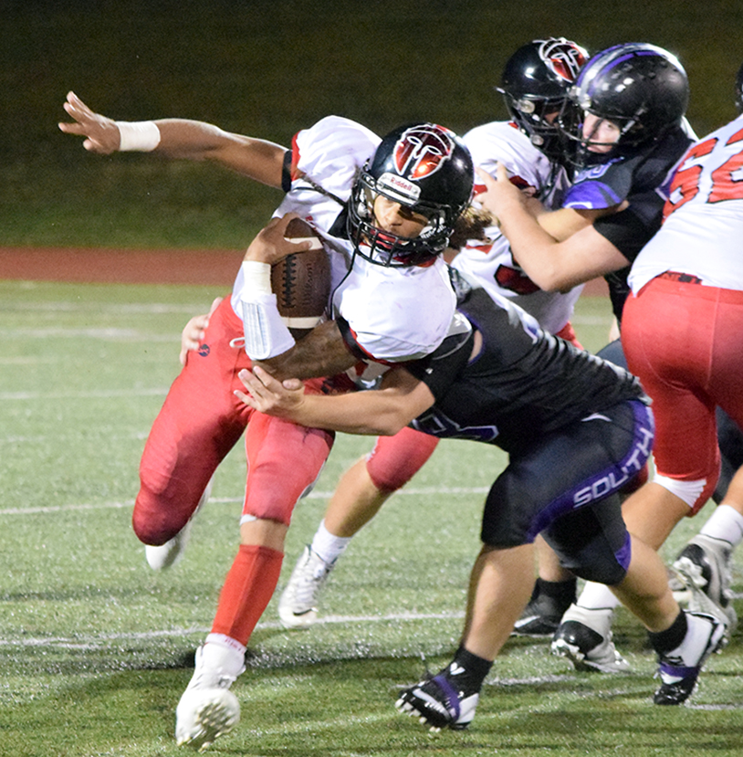 BRYCE MERENESS/Citizen photo Park Hill senior running back Zach Neal, left, attempts to break a tackle from Park Hill South linebacker Tristan Uribe during a game on Friday, Sept. 18 at Park Hill District Stadium in Kansas City, Mo.
