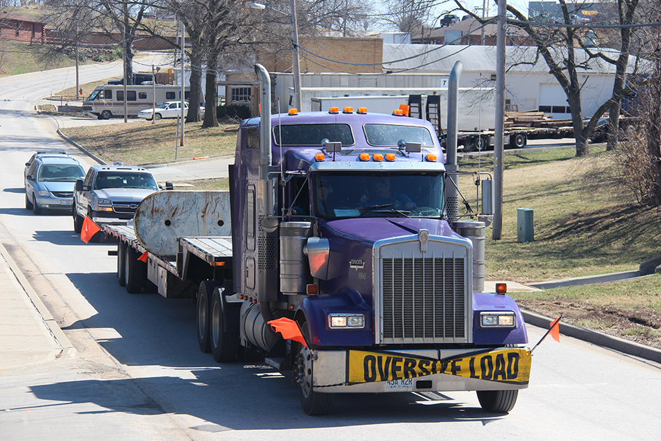 ROSS MARTIN/Citizen photo A semi truck and flat-bed trailer from Kerwin Transport of Platte City carries a 13-ton anchor off of the USS Platte (AO-186) with a convoy along Main Street on the afternoon of Friday, March 20. The relic came off a decommissioned Naval ship named for the Platte River. Platte City mayor Frank Offutt secured the item as a donation and intends to use it this summer during a ceremony for the 175th anniversary of the city's founding. The anchor currently rests in the park, while awaiting a more permanent display setting.