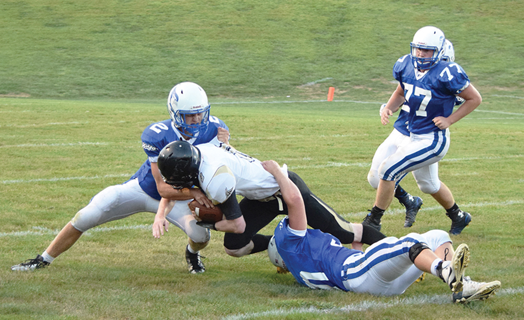 BRYCE MERENESS/Citizen photo West Platte seniors Brett Shepardson, left and Dalton Larison, bottom, attempt to bring down Lathrop senior Cody Hart, center, during a game on Friday, Sept. 11 at Rudolph Eskridge Stadium in Weston, Mo.