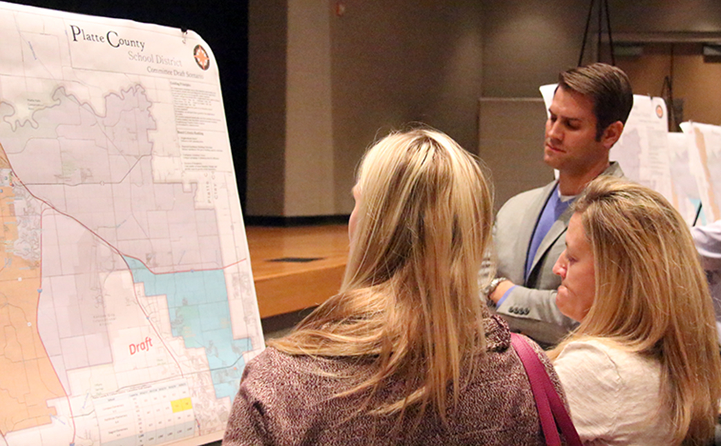 ROSS MARTIN/Citizen photo Ryan McKay (rear), senior planner with RSP Associates, looks over a draft of a Platte County R-3 School District boundary map for elementary attendance centers during a public forum held Thursday, Nov. 19 at Wilson Center for Performing Arts at Platte County High School. School district patrons are encouraged to submit feedback through its website with the board of education scheduled to make a final decision in December.