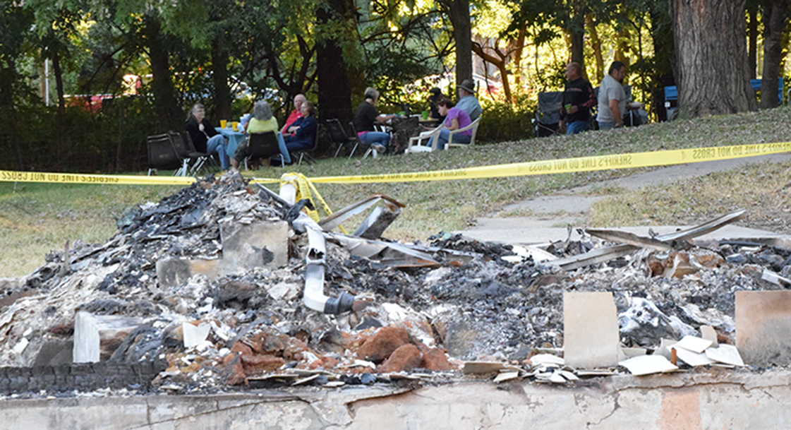 BRYCE MERENESS/Citizen photo Attendees of the Short Creek Baptist Church's annual hog roast, held Saturday, Sept. 19, enjoy food and drink in the shadow of the burned out remains of the building near Rushville, Mo. The 120-year-old church burned to the ground one week earlier.
