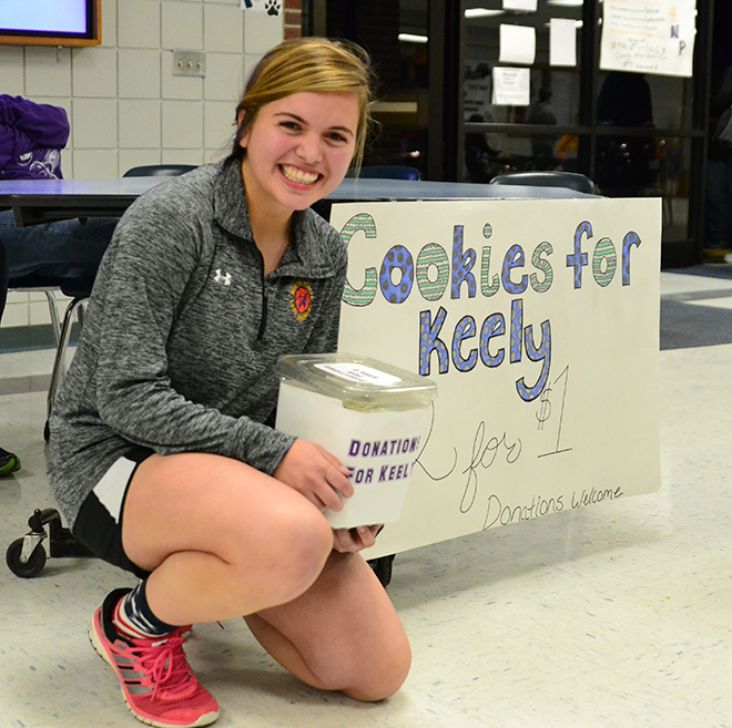 BRYCE MERENESS/Citizen photo North Platte senior Courtney Kipping poses in front of a table she set up Friday, Feb. 6 during a basketball doubleheader between the Panthers and Lathrop to sell cookies in order to raise money for a Lawson, Mo. family that recently lost its home in a fire. Keely Simmons, a member of that family, plays for the Lawson girls basketball team, and the money raised was presented to her during a game between North Platte and Lawson on Tuesday, Feb. 10 at Lawson High School.