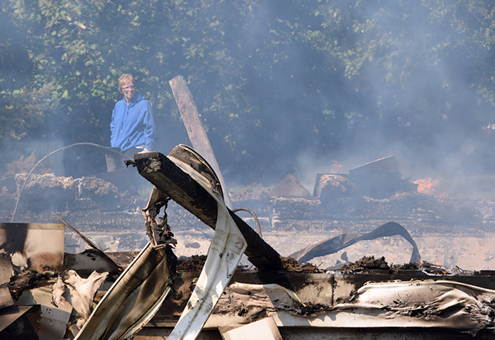 BRYCE MERENESS/Citizen photo Sara Brown of Rushville, Mo. examines the remains of the Short Creek Baptist Church on Saturday, Sept. 12 after a fire leveled the 120-year-old building located in rural northwestern Platte County.