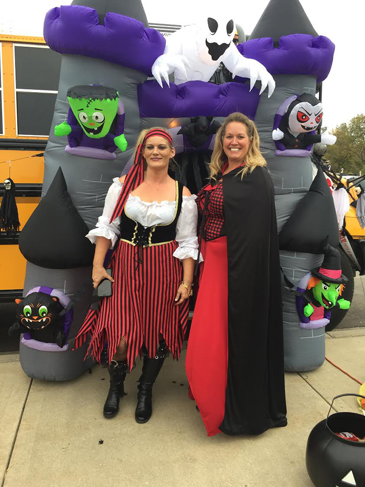 "Contributed photo Melissa O'Connell, left, and Candice Rivera Roman pose outside of the ""haunted bus"" they created for a Trunk n Treat event at Pathfinder Elementary in late October. The event drew hundreds, and students were able to take a trip through the bus in addition to the normal candy handouts. The Platte County R-3 School District honored the two bus drivers for their work on the project during a recent board meeting."