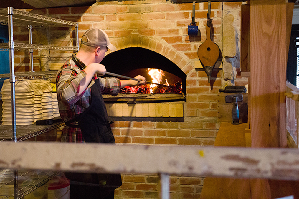 CORY MACNEIL/Citizen photo Dylan Low tends to the wood fire in the brick oven he built for his business, Hearth Bread Company in Weston, Mo. The 21-year-old owns and operates the bakery.