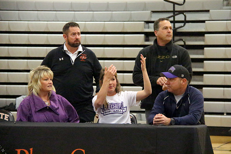 ROSS MARTIN/Citizen photo Platte county senior shortstop Jessie Hoover, center, waves to assistant coaches Lauren Barker and Steve Elliott to join her at a ceremony announcing she will play  softball at the University of Central Arkansas during a ceremony Nov. 19 at Platte County High School.