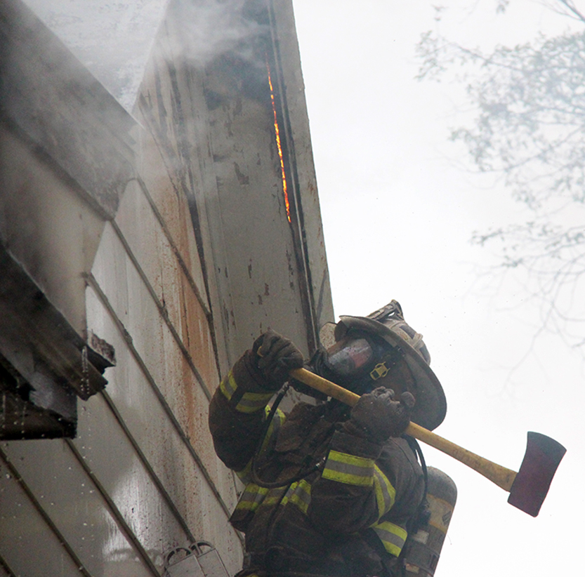 ROSS MARTIN/Citizen photo A firefighter uses an ax in an attempt to punch a hole in the wall of a house Wednesday, Nov. 4 while battling a structure fire on Fourth Street in Dearborn, Mo.