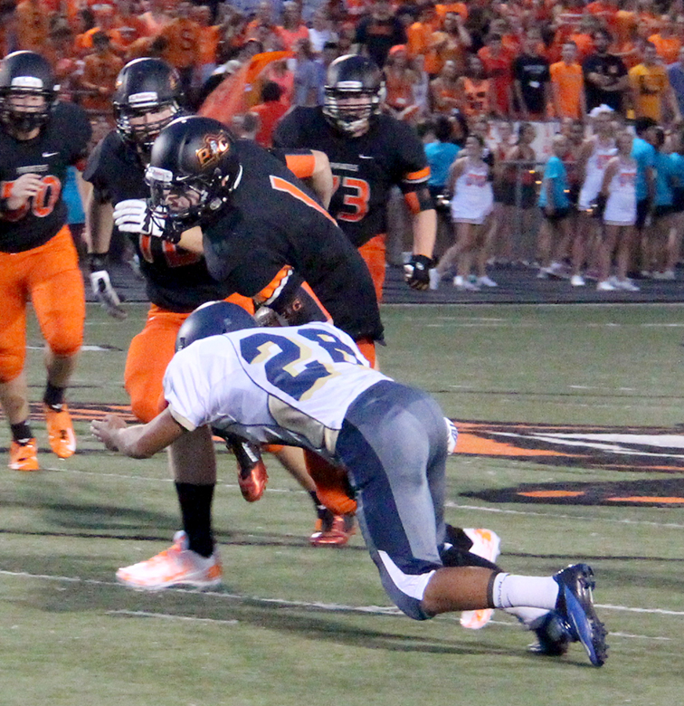 ROSS MARTIN/Citizen Photo Platte County quarterback Justin Mitchell lowers his shoulder in an attempt to gain more yards while William Chrisman's Kyron Mason  (28) tries to make the stop Friday Aug. 20 at Pirate Stadium.