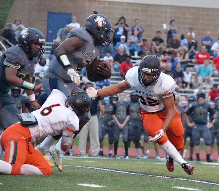 ROSS MARTIN/Citizen photo Platte County senior Christian Encarnacion, right, lines up a tackle while junior Cade Goettling (6) grabs William Chrisman quarterback Bailey James Jr.'s ankle during Platte County's season-opening win against William Chrisman on Friday, Aug. 21 at William Chrisman High School in Independence, Mo.