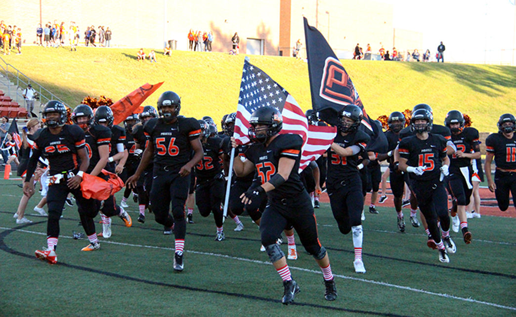 ROSS MARTIN/Citizen photo Platte County senior defensive lineman Bryan Meyerowich carries the American flag onto the field Friday, Sept. 11 at Pirate Stadium before the game against Park Hill South. Platte County players honored the anniversary of the Sept. 11, 2001 terrorist attacks by wearing American flag socks.