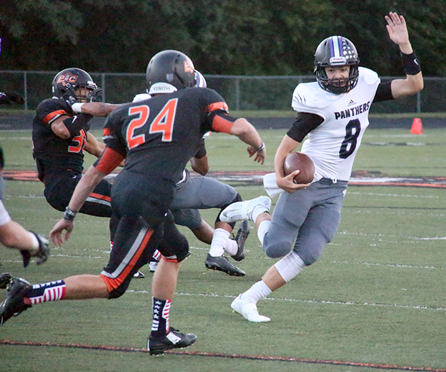 ROSS MARTIN/Citizen photo Park Hill South quarterback Zach Suchanick, right, attempts to evade Platte County senior linebacker Johnny Blankenship (24) during a game Friday, Sept. 11 at Pirate Stadium.