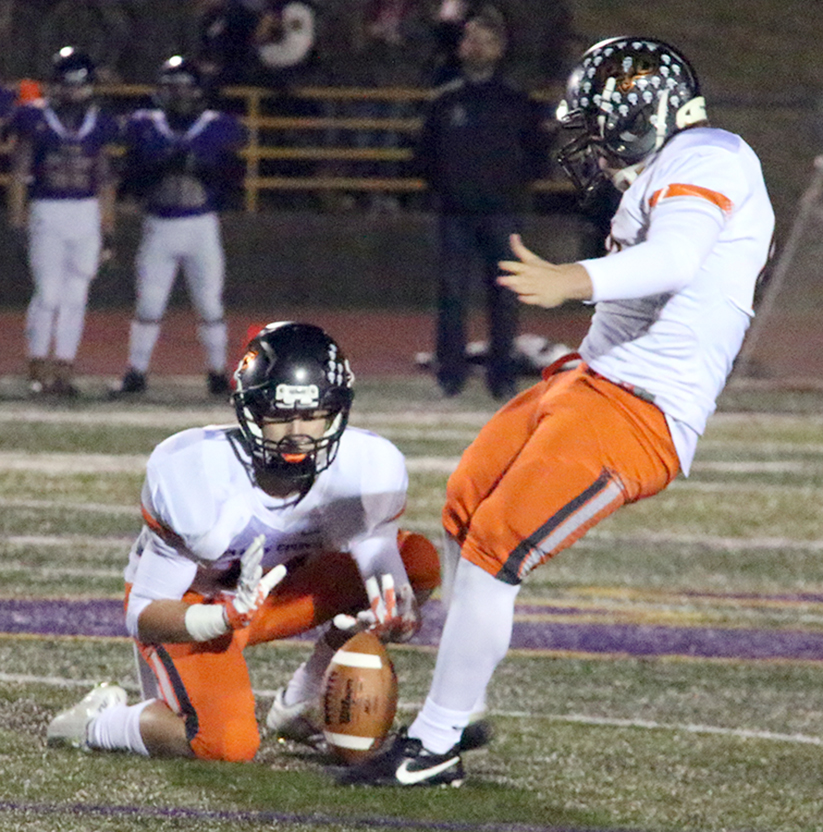 Platte County sophomore kicker Parker Lacina boots a school-record 53-yard field goal out of the hold of junior Carter Nugent, left, during the Class 4 District 8 championship game against Kearney on Friday, Nov. 6 at Kearney High School in Kearney, Mo.