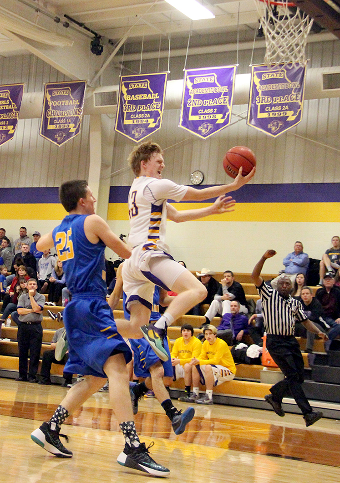 ROSS MARTIN/Citizen photo North Platte senior guard Andrew Roberts, right, goes up for a layup while drwing a foul on East Buchanan's Logan Spencer during a KCI Conference matchup Friday, Dec. 18 at North Platte High School.