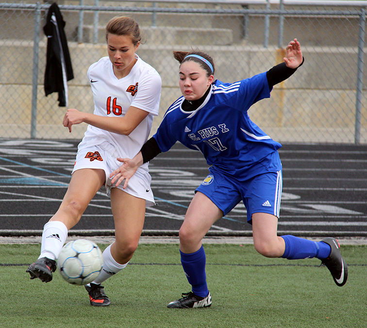 ROSS MARTIN/Citizen photo Platte County sophomore Katana Audas, left, attempts to dribble past St. Pius X defender Sydney Routh during the fifth-place match Platte County Invitational on Friday, March 27 at Pirate Stadium