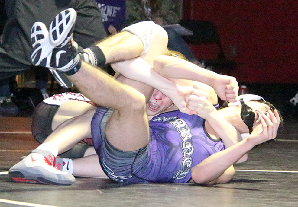 ROSS MARTIN/Citizen photo Park Hill sophomore Josh Steele, rear, holds Kearney's Clayton Singh in a cradle during a 113-pound match Friday, Jan. 8 at Park Hill High School in Kansas City, Mo.