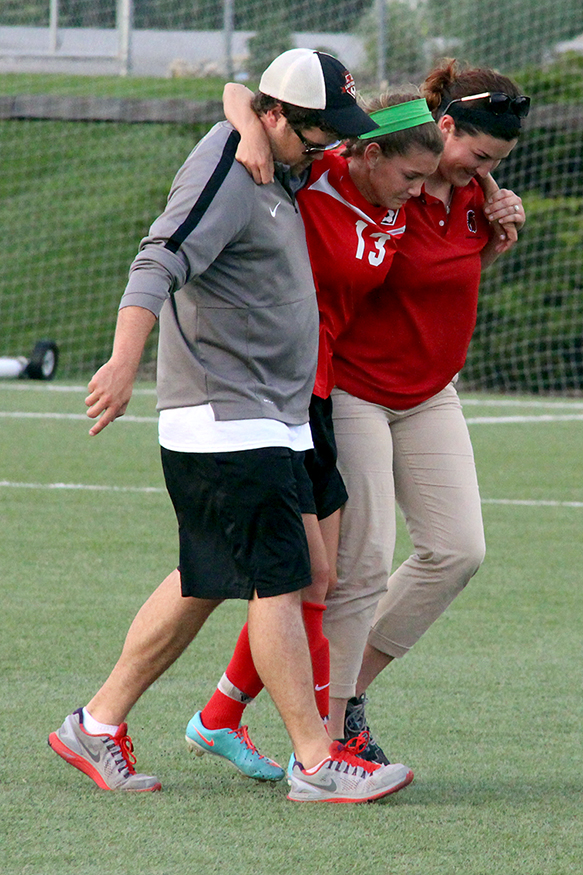 Park Hill sophomore defender Jenna Winebrenner, center, limps off the field with assistance from a trainer and Trojans coach Brandt Bell, left, after she injured her knee in the first half.