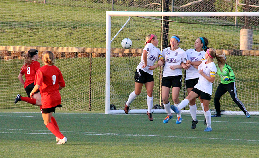 ROSS MARTIN/Citizen photo Park Hill's Bella Catano (9) fires in a free kick, while Park Hill South's Shay Jackson, left, turns her head in the wall during a game Thursday, May 14 at Park Hill Soccer Complex in Riverside, Mo.