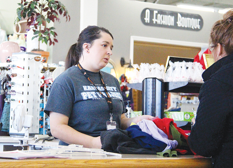 ROSS MARTIN/Citizen photo Karegan Turner, a Platte County High School graduate, talks with a customer at the Hillcrest Thrift Shop's registers. She continues to volunteer at Hillcrest in her spare time while also attending classes at Maple Woods Community College in Kansas City, Mo.