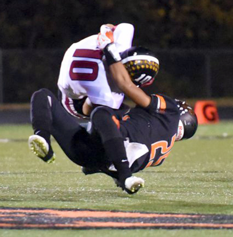 TODD NUGENT/Special to The Citizen Platte County sophomore defensive back Kobe Cummings, bottom, wraps up and tackles St. Joseph Benton quarterback Cooper Burton during  a first-round Class 4 District 8 matchup Friday, Oct. 23 at Pirate Stadium.