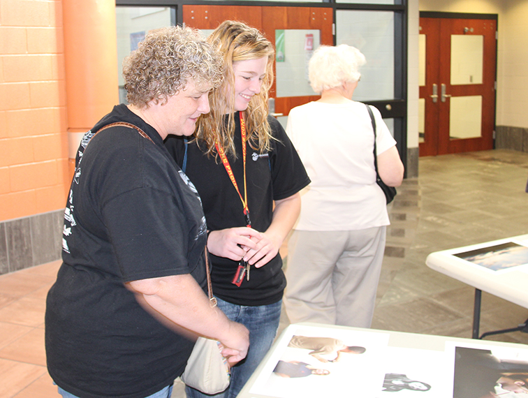 ROSS MARTIN/Citizen photo Jacinda Odell (right), 19, looks at photographs of herself during a Sept. 27 exhibit at Platte City Middle School of work completed during Missouri Photo Workshop 66, which annually chooses a different city. MPW 66 brought 43 photographers to Platte City to capture unique stories last week.