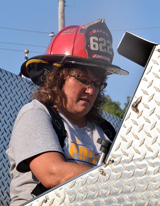 BRYCE MERENESS/Citizen photo Michelle Johnson demonstrates working the pump controls on the Dearborn Area Fire Protection District truck Saturday, Aug. 22 in Dearborn, Mo. In addition to her volunteer firefighting duties, she also serves as North Platte junior and senior high school principal.