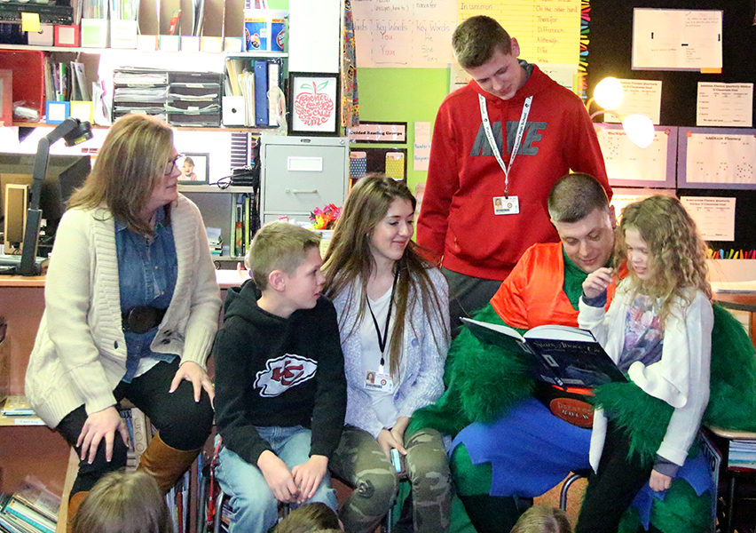 ROSS MARTIN/Citizen photo Lt. Col. Myles Perry, at right with the book, returned Tuesday, Dec. 2 from a tour of duty with the Army Reserves in Afghanistan. He made a surprise homecoming visit to Siegrist Elementary in Platte City. Pictured with him, from left are wife Marsha and their kids Carson, 12, Kendall, 16, Braeden, 16, and Emerson, 9.