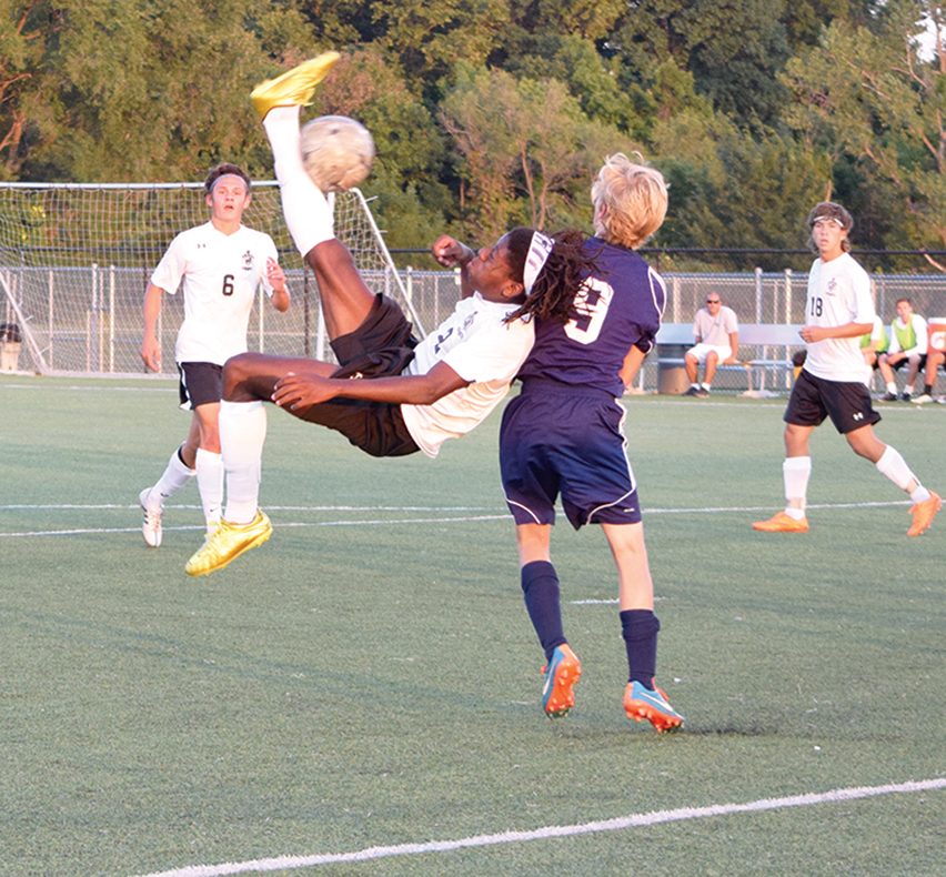 BRYCE MERENESS/Citizen photo Park Hill South forward Nylo Clarke, center airborne, attempts a bicycle kick past St. Joseph Central midfielder Gaige Wilson (9) on Monday, Sept. 14 at Park Hill District Soccer Complex in Riverside, Mo.