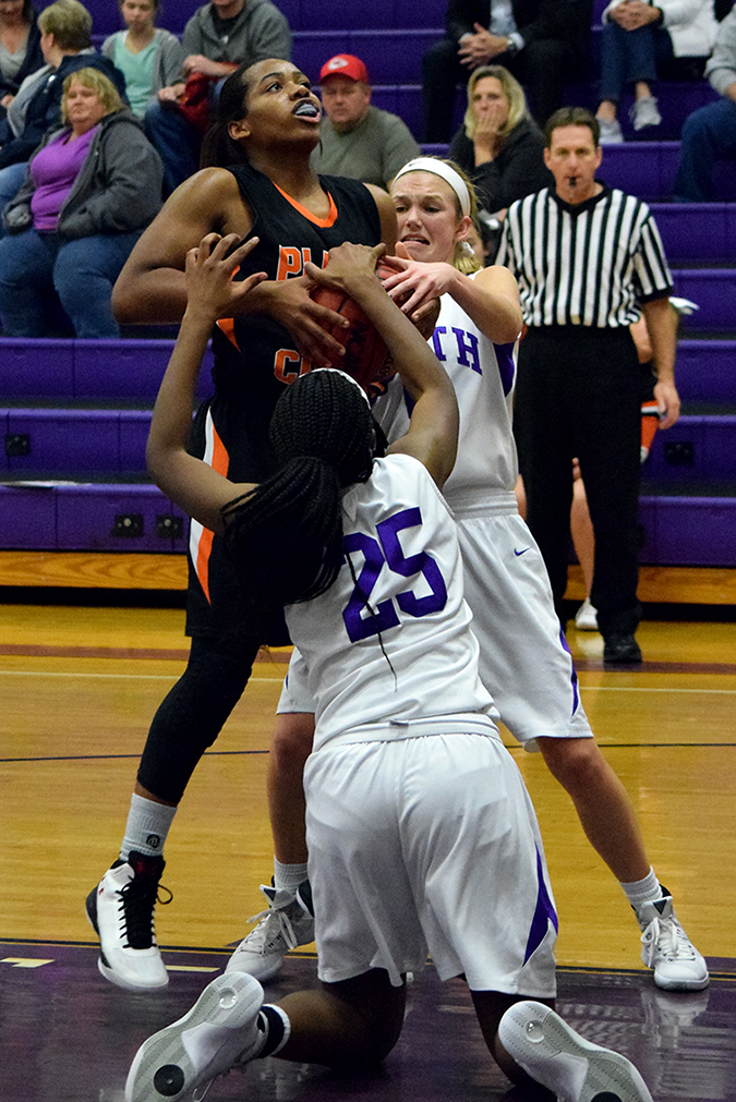 BRYCE MERENESS/Citizen photo Park Hill South freshman forward Alecia Westbrook (25) and junior guard Grace Cunningham, right, tie up Platte County sophomore guard Rocky Chambers on Thursday, Dec. 10 at Park Hill South High School in Riverside, Mo.
