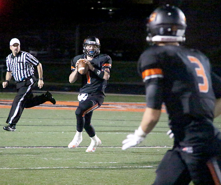 ROSS MARTIN/Citizen Photo Platte County quarterback Justin Mitchell, center, rolls out to pass last Friday at Pirate Stadium while wide receiver Tyler Cooper (3) runs a route against St. Joseph Central.