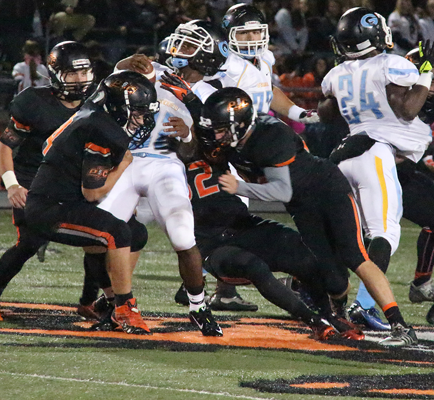 ROSS MARTIN/Citizen photo Platte County defenders Tyler Blankenship, left, Christian Encarnacion, center, and Johnny Blankenship, right, tackle grandview running back Ja'Kori Bell during the Oct. 10 game at Pirate Stadium.