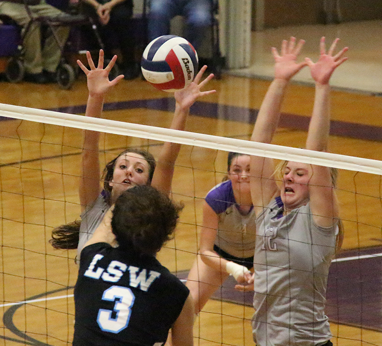 ROSS MARTIN/Citizen photo Park Hill South's Bri Bartosh, left, and Andi Elley, right, attempt to block a spike from Lee's Summit West's Taylor Akason (3) in a match Oct. 9 at Park Hill South High School in Riverside, Mo.