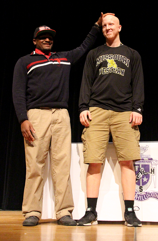 ROSS MARTIN/Citizen photo Park Hill South senior Jordan Bell, left, rubs the head of teammate Tyler Baska after they signed to play collegiate football during a ceremony Wednesday, Feb. 2 at Park Hill South High School in Riverside, Mo.