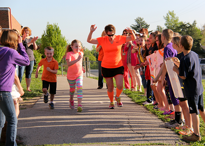 Contributed photo Missy Beatty, a music teacher in the Park Hill School District, holds a ceremonial start for her goal to run 130 miles this month during a ceremony Friday, May 1 at Chinn Elementary School in Kansas City, Mo. The miles are part of a fundraiser to help her brother, who was recently diagnosed with cancer.