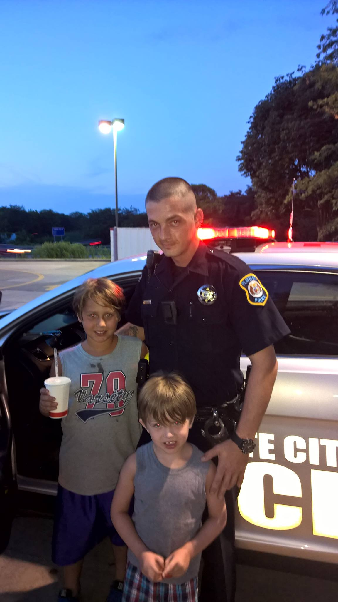 Contributed photo Platte City Police Department officer Andy Servaes poses with Thomas Palmer, 9, and Logan Trucke, 5, of Iowa outside of the Arby's restaurant in Platte City on Friday, Aug. 7. The photo, posted to Facebook, went viral after Servaes spent his dinner break that night answering the boys' questions and showing them his patrol vehicle.