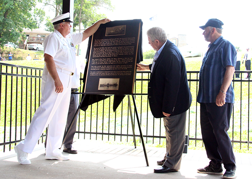 ROSS MARTIN/Citizen photo Charles Schley (left), a retired Chief Boatswain's Mate in the U.S. Navy, unveils a plaque dedicated to the permanent display of an anchor off of the USS Platte (AO-186), a decommissioned Cimarron class fleet oiler. Schley served on the commissioning crew for the USS Platte, the second boat to bear the name of the Platte River. The plaque was shown to the public during a ceremony held Saturday, July 4 at Settler's Crossing Park in Platte City that also celebrated the 175th anniversary of the city's founding. Schley flew in from Pennsylvania to be a guest of honor.