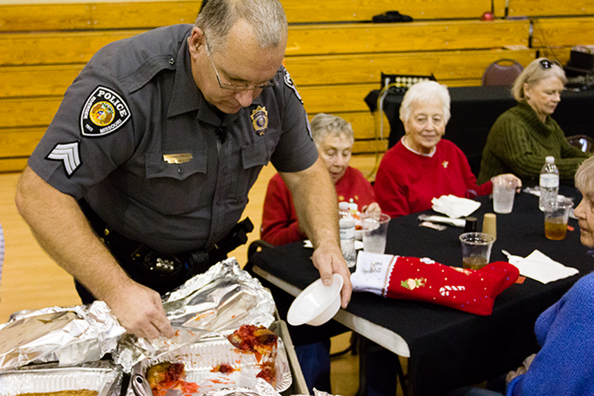 CORY MACNEIL/ Citizen photo Sgt. Jack Minor of the Riverside Police Department serves cherry cobbler to guests at the City of Riverside's annual seniors holiday dinner held Tuesday, Dec. 8 at Riverside Community Center in Riverside, Mo.