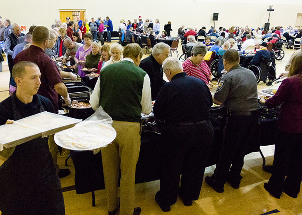 CORY MACNEIL/Citizen photo Public servants in Riverside, including fire and police personnel, work to serve a holiday meal to the city's senior citizens during an annual event held in the gymnasium at the Riverside Community Center in Riverside, Mo. The workers prepare and serve the food to dozens of guests.