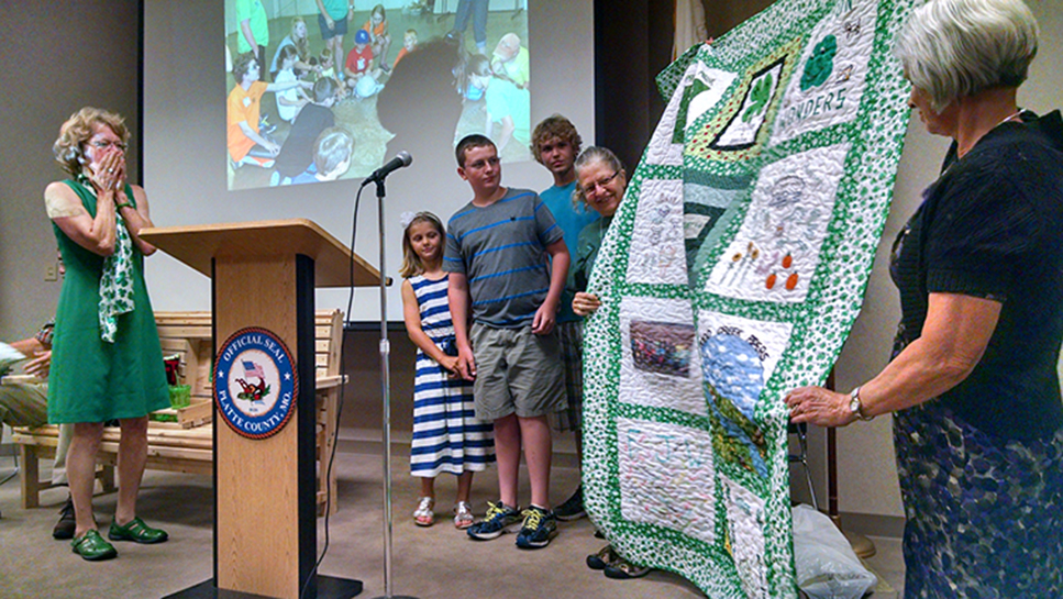 JEANETTE BROWNING FAUBION/Citizen photo Sharen Hunt, left, reacts as Ladybugs and Beetles 4-H Club present her with a hand-made quilt featuring squares from past and present 4-H clubs. The presentation was made during a farewell reception held in Hunt's honor on Sunday, Aug. 9 at the Platte County Resource Center in Kansas City, Mo. Hunt served the University of Missouri Extension Council and 4-H in Platte County for 37 years.