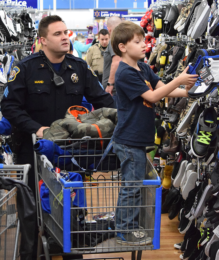 BRYCE MERENESS/Citizen photo Platte City Police Department Sgt. Mike Mand helps a Shop with a Cop participant pick out items during the annual event held Saturday, Dec. 5 at the Wal-Mart on Boardwalk Square in Kansas City, Mo. For the sixth year, Platte City PD participated and helped buy gifts for underprivileged youths through donations and fundraisers.