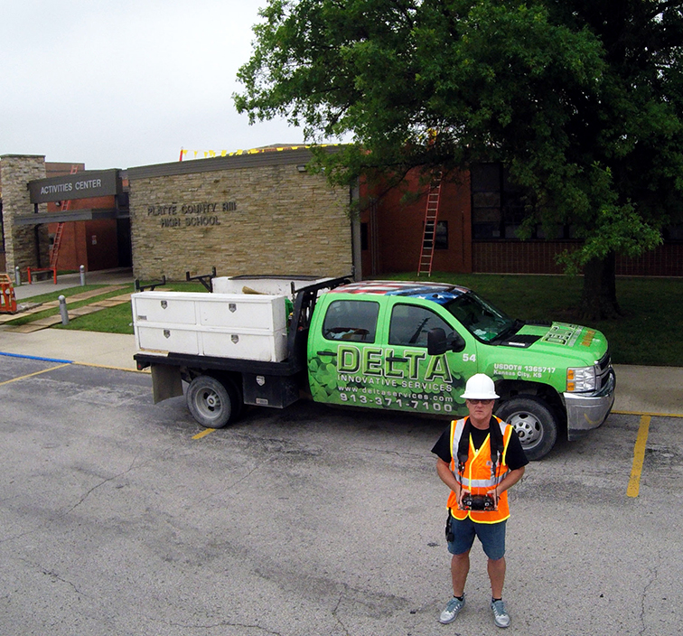 Contributed photo Mike Raymond controls his unmanned aerial vehicle to take a picture of himself outside of Platte County High School. Aerial Logic Roof Inspections, his business, recently helped Delta Innovative Services with a roofing project for the district.
