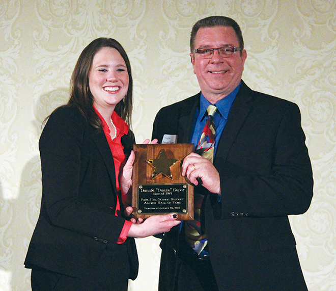 ROSS MARTIN/Citizen photo Platte County second district commissioner Duane Soper poses with hall of fame plaque, alongside master of ceremonies Brooke Rohlfing, the district's broadcast production specialist.