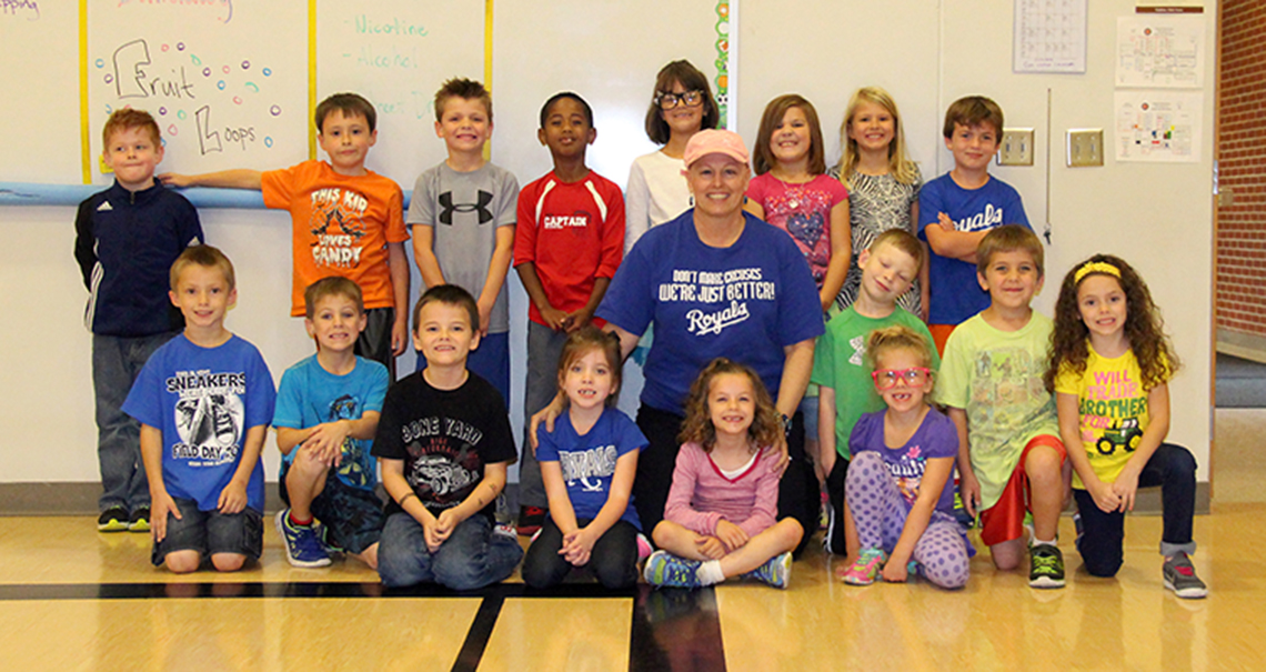 ROSS MARTIN/Citizen photo Stephanie Jermain, center, poses with her first grade class days after ditching her wig to show the effects of her chemotherapy, which included total hair loss. She used her story to teach them lessons about perseverance and empathy.