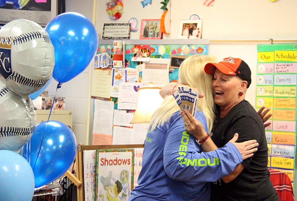 ROSS MARTIN/Citizen photo Stephanie Jermain — pictured at right, a first grade teacher at Siegrist Elementary in the Platte County R-3 School District — receives four free tickets ahead of Game 6 of the American League Championship Series between the Kansas City Royals and Toronto Blue Jays. Amy Acock (left), a represenative with Academy Sports+Outdoors and a North Platte graduate, made the presentation. The company heard about Jermain's inspirational fight with an aggressive form of breast cancer and decided to donate the tickets to recognize her dedication to raising awareness for the need of regular self exams to help detect cancer early.