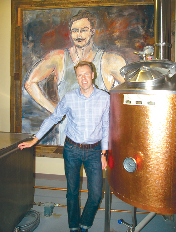 JEANETTE BROWNING FAUBION/Citizen photos ABOVE: Steve Strong stands next to his still and a fitting painting for his S.D. Strong Distillery products. Strong operates his distillery out of the Park University Underground caves in Parkville, Mo.