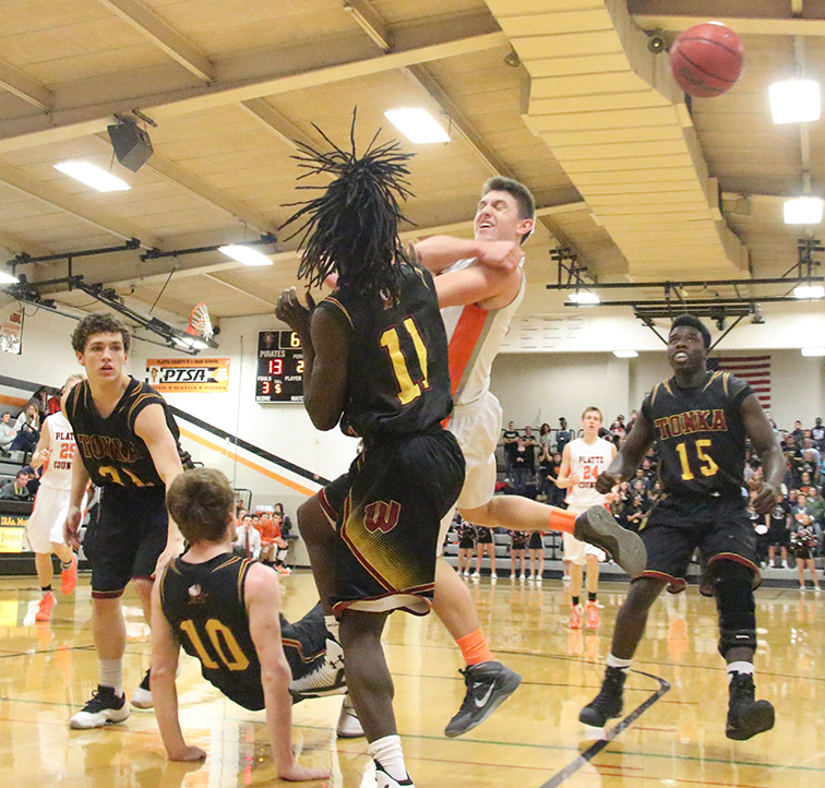 ROSS MARTIN/Citizen photo Platte County guard Topher Kilkenny, rear center, makes a pass while running into Winnetonka's Willy Majok (11) during a game on Friday, Feb. 27 at Platte County High School.