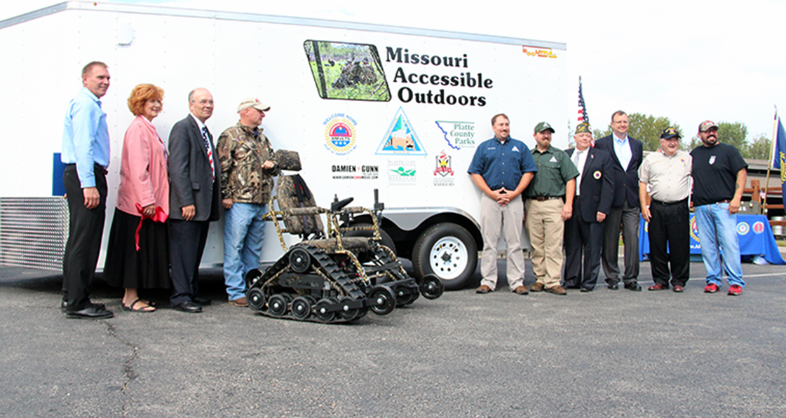 ROSS MARTIN/Citizen photo Donors and government officials pose for a photo during a ceremony held Tuesday, Sept. 15 at Parma Woods Shooting Range in rural Parkville, Mo. With fundraising and government grants, the specialized track chair seen in the foreground was purchased and donated to the Missouri Department of Conservation, which will house and rent out the unit to disabled residents of Platte County.