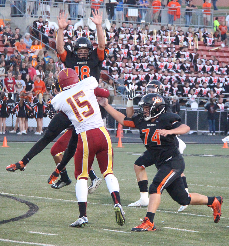 Platte County linebacker Tyler Clemens (18) attempts to bat down a pass from Winnetonka quarterback Julious Sabastiano (15) while Tyler Blankenship (74) applies pressure Friday at Pirate Stadium. Platte County won 35-19 to improve to 5-0 on the season.