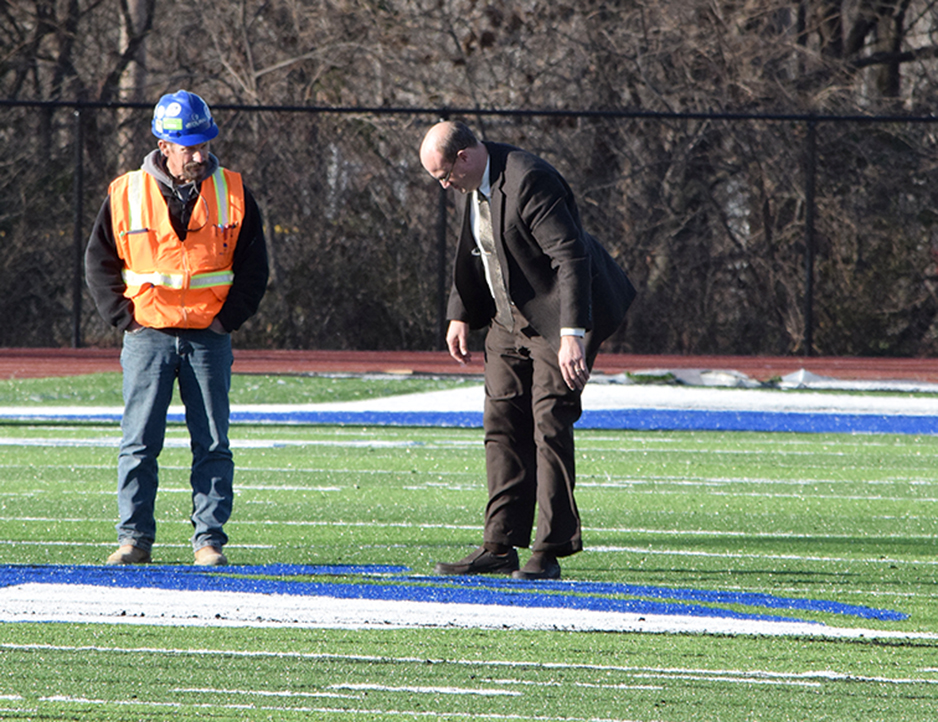 BRYCE MERENESS/Citizen photo West Platte superintendent John Rinehart, right, and JE Dunn Construction superintendent Dale Duncan, left, inspect the recently installed turf at West Platte's new athletic stadium Monday, Dec. 7.