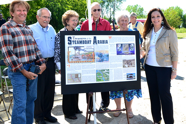 BRYCE MERENESS/Citizen photo From left: David Hawley, Bob Hawley, Flo Hawley, Jerry Mackey, Joan Mackey and Parkville mayor Nan Johnston pose with a mockup of a historical marker during a ceremony Sept. 6 at Platte Landing Park in Parkville, Mo. honoring the sinking of the Steamboat Arabia near the area. A permanent marker will go up soon nearby.