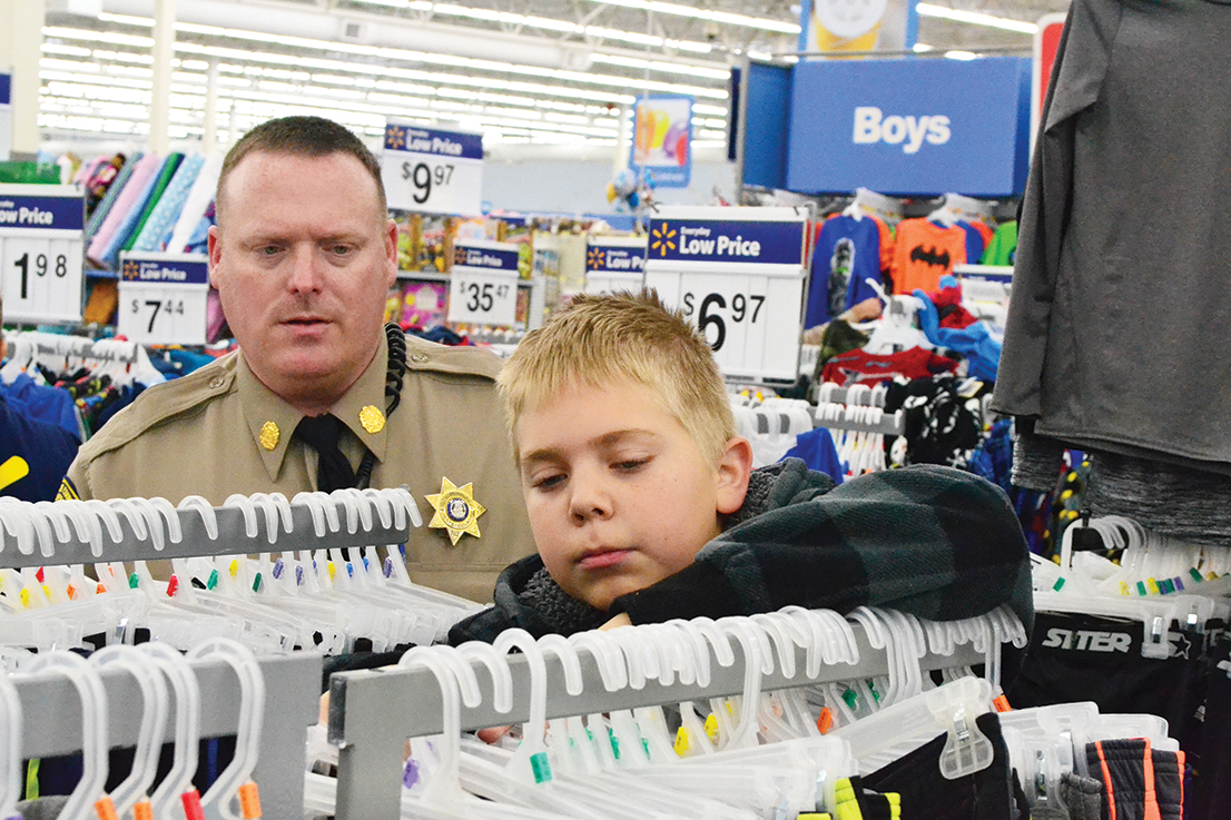 BRYCE MERENESS/Citizen photo Platte County Sheriff's Office deputy Gabriel Mountain, left, looks on as Taylor picks out items during the 20th annual Shop with a Deputy event held the morning of Saturday, Dec. 6.